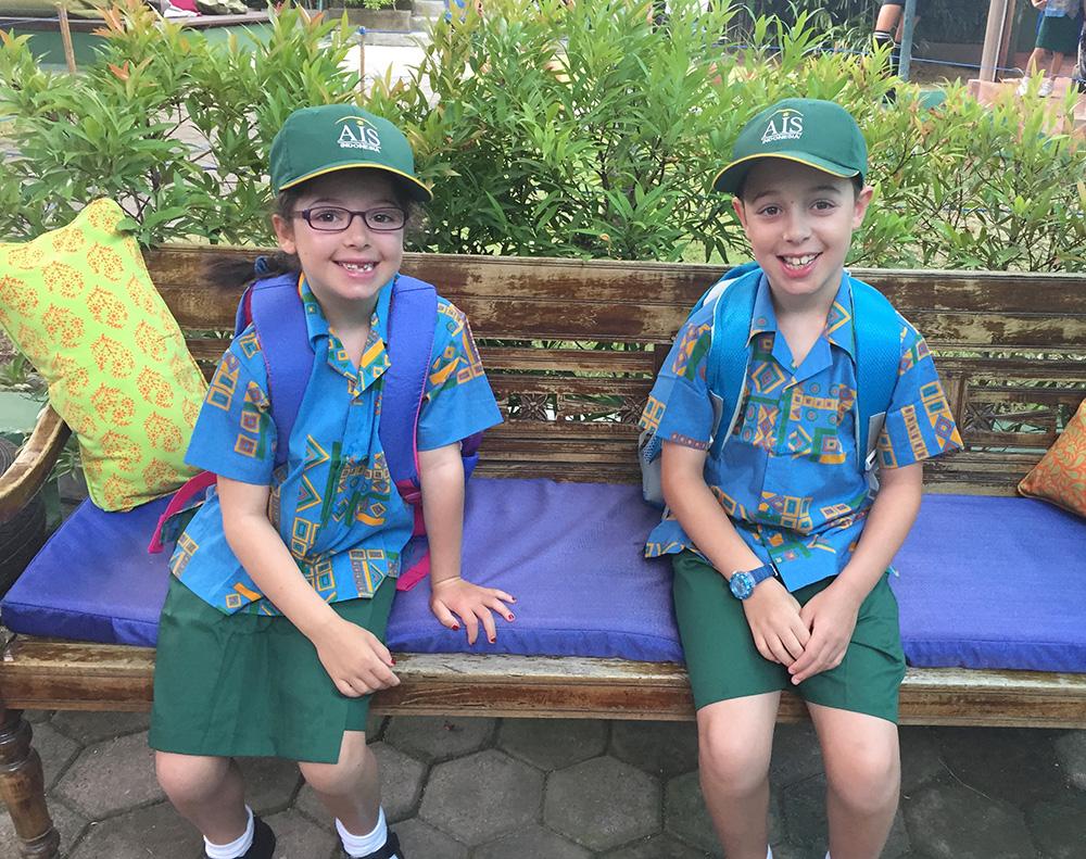 Two children smile at the camera, wearing Bali's Australian Independant School uniform