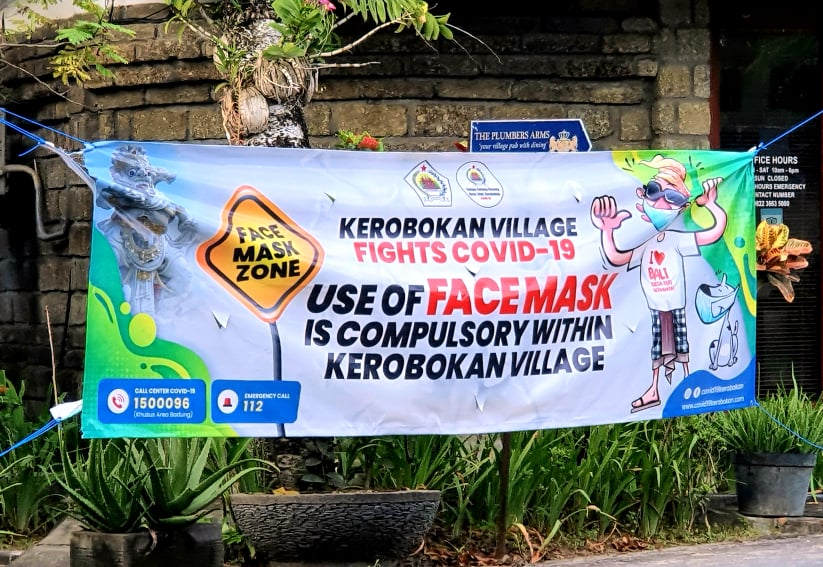 A banner in Kerobokan Village, Bali, notifying passes by to wear their masks during the COVID-19 Pandemic.