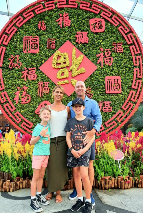 The Zubak family together in front of a Balinese Chinese New Year art piece.
