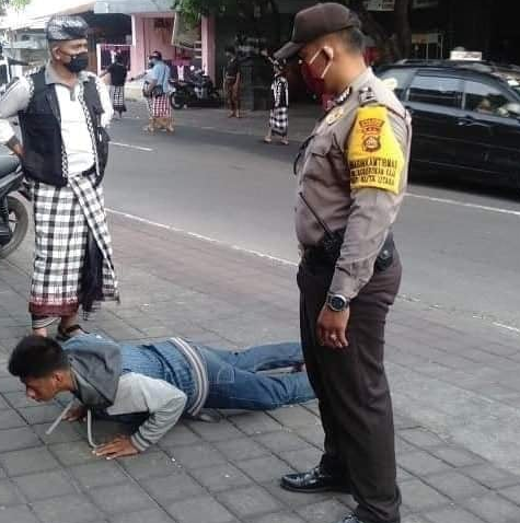 A local Balinese man lies on the street doing push-ups in front of a policeman for not wearing a facemask.