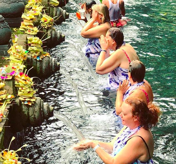 Jules Thomson's Indah Escapes Tour Group at the Tirta Empul temple, a Hindu Balinese water temple.