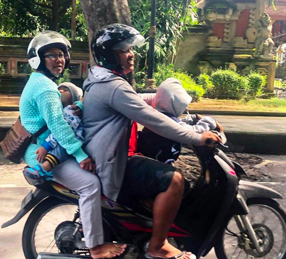 A Balinese mother and father, with two children, ride through Sanur, Bali, on a motorbike.