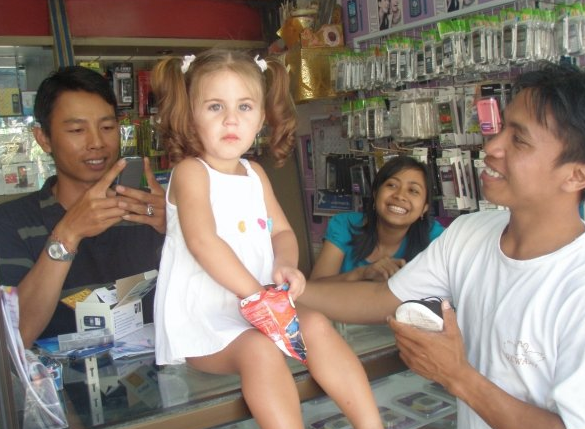 Lee Anna's daughter, Shanti, being admired by Balinese locals at a SIM card store.