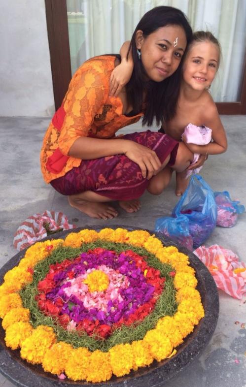 Lee Anna's daughter, Shanti, hugging a local Balinese woman wearing a Kebaya.