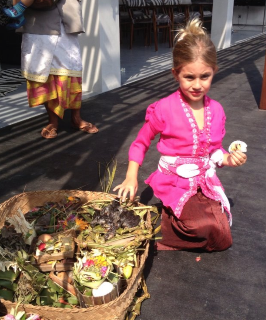 Lee Anna's daughter, Shanti, dressed in traditional Balinese kebaya and participating in a local Balinese ceremony.