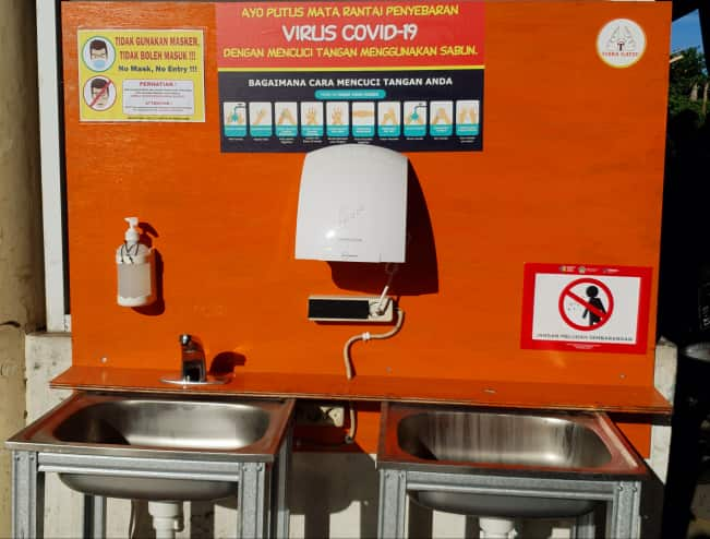 A handwashing station outside of a Balinese supermarket featuring warnings and recommendations to prevent the spread of COVID-19.
