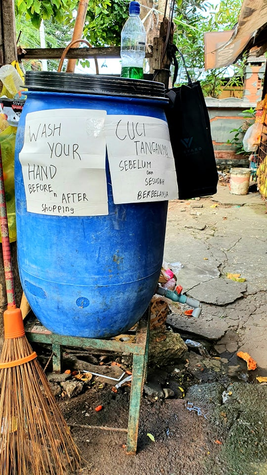 A water drum with signs in English and Bahasa advising locals to wash hands before and after shopping.