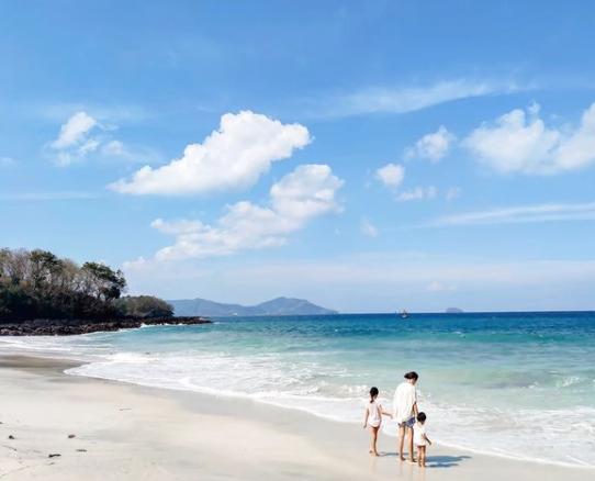 Indonesian family on the sand on Padang Bai beach, Bali