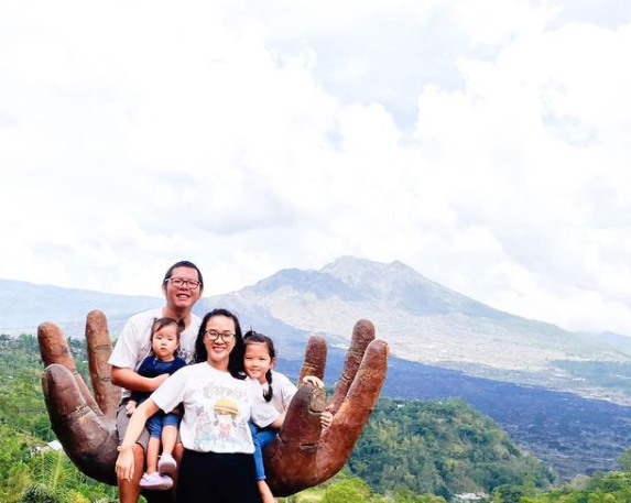 Indonesian family posing on hill in Kintamani, Bali, Indonesia
